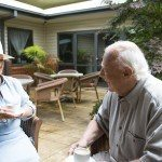 Image of couple sitting in the garden talking at Greenway Gardens